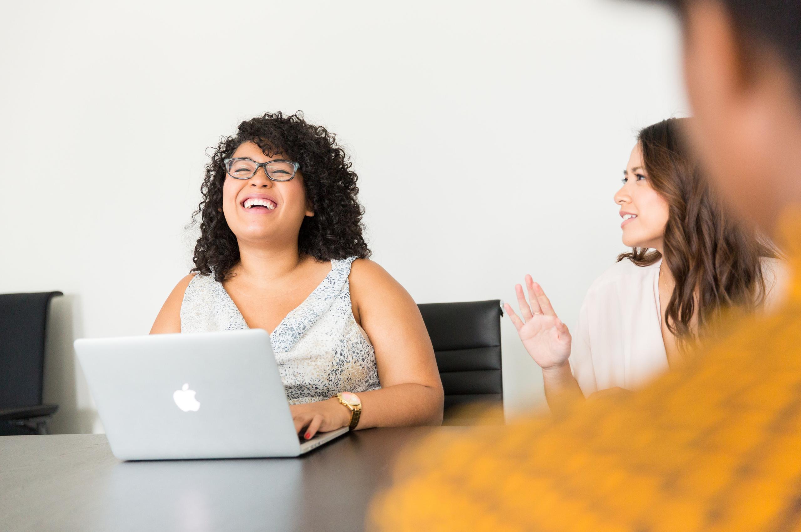 woman laughing behind macbook